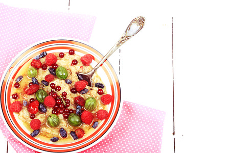 breakfast oatmeal with berries and honey on white wooden background flat style top view overhead summer menu Reklamní fotografie