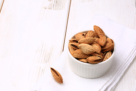 almonds in shell on a white wooden background Imagens