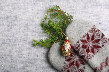 Warm Christmas. Knitted mittens and a Christmas tree. New Year holiday background