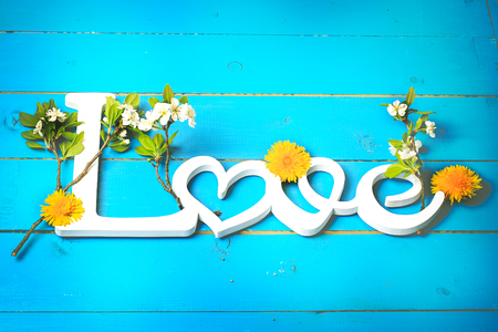 word love on wooden background with spring flowers. Valentines day Imagens