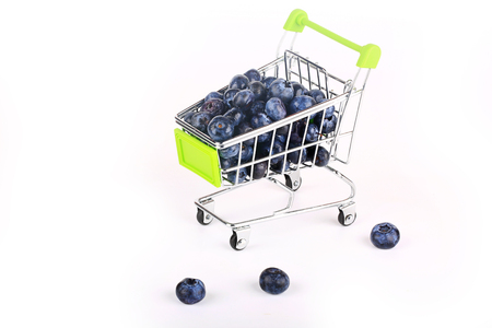 Blueberry berries in a shopping trolley isolated on white background