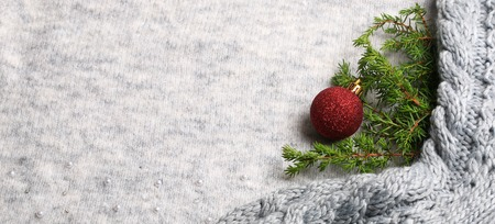 New Year holiday background. Christmas tree toy and a spruce branch on a knitted gray background. Christmas composition Imagens