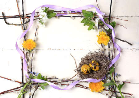 Easter frame background nest with painted egg willow flowers dandelions on a white wooden background top view