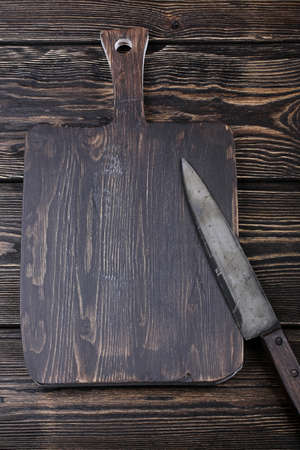 cutting board with a knife for slicing on the old wooden background with space for text