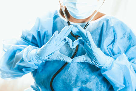 Woman doctor shows heart with hands. Doctor's love for patients. Doctor for the heart. Concept of Covid-19 quarantine. Medical concept.