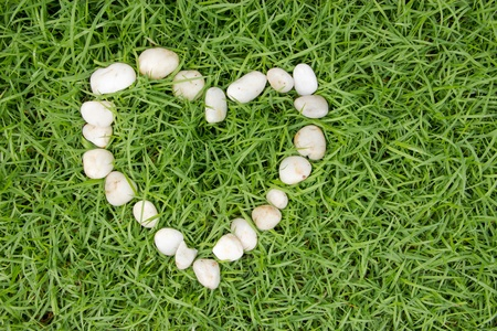 white stones in heart shape on fresh green grass