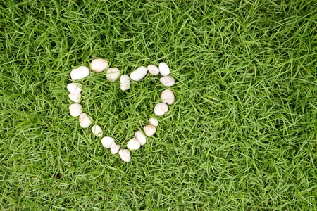 white stones in heart shape on fresh green grass photo