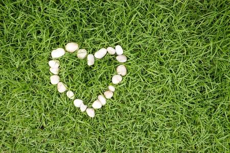 white stones in heart shape on fresh green grass
