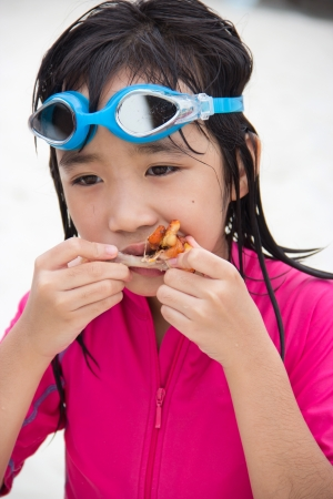 cute asian girl eating chicken on the beach