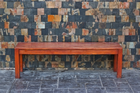 wooden bench with stone wall photo