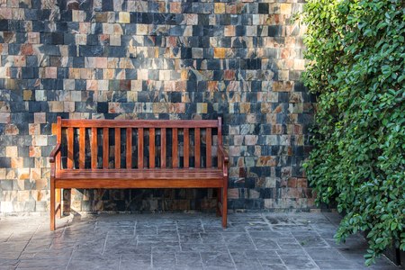 sidewalk scene with wooden bench and wall