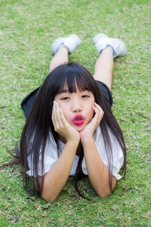 Asian girl lying on green grass Stock Photo