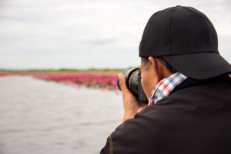 Middle-aged man take photograph at the lake Stock Photo