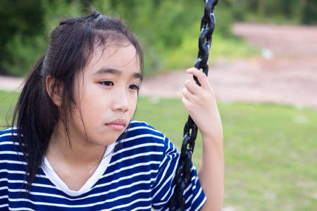 Asian girl in a bored mood at playground.