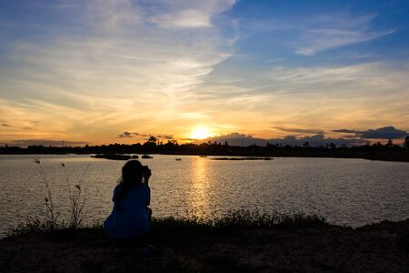 love pic: Asian girl taking picture with mobile phone at lake on sunset.