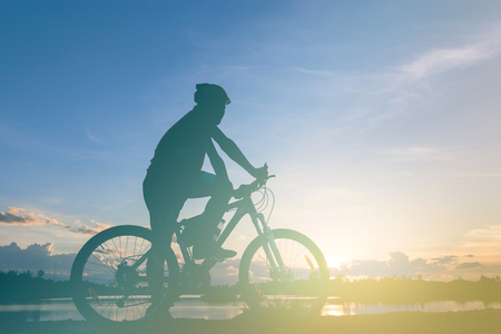cycler: biker silhouette at lake in sunset.