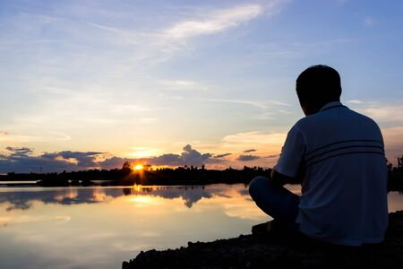 sit down: man sit down and take photo by camera at lake with sunset sky. Stock Photo