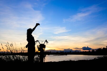 love pic: Asian girl taking picture with bike by mobile phone at lake on sunset. Stock Photo