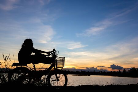 love pic: Silhouette Asian girl relax on bike at lake on sunset.