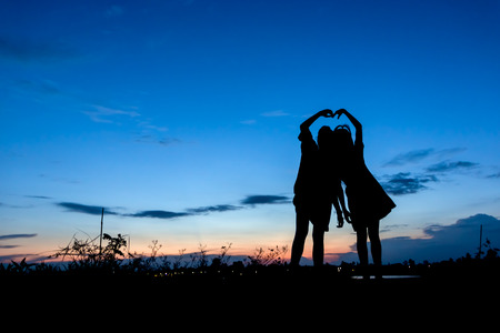silhouette of two girls are frinds take photo with sunset.