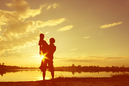 lake sunset: Silhouette Father and daughter playing at lake at the sunset time. Concept of friendly family.Fill color filter.