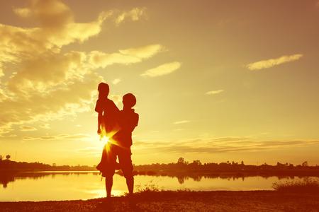 dadã  daughter: Silueta Padre e hija jugando en el lago en la puesta del sol. Concepto de amigable filtro de color family.Fill.