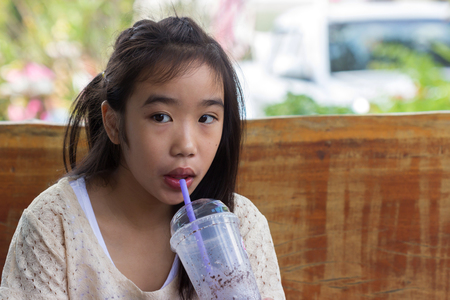 Little Asian girl with ice chocolate