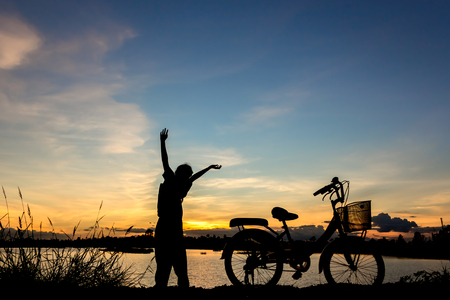 fit girl: Biker-girl at the sunset  at lake.