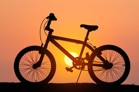 silhouette bicycle on grass in the evening: Stock Photo