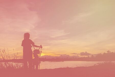 love pic: Asian girl taking picture with mobile phone on sunset. Fill color filter. Stock Photo