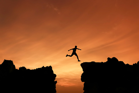 difficult lives: Silhouette Freedom-young man is jumping over precipice between two rocky mountains at sunset.
