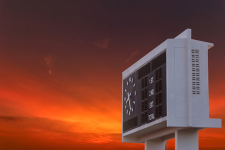 Blank scoreboard at outdoor stadium with sunset sky. Stock Photo