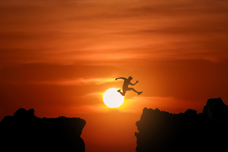 Silhouette Freedom-young man is jumping over precipice between two rocky mountains at sunset.
