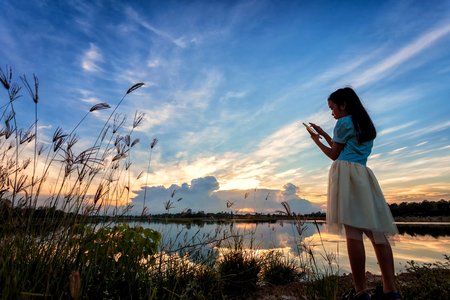 Asian girl taking picture  by mobile phone at lake on sunset. Stock Photo