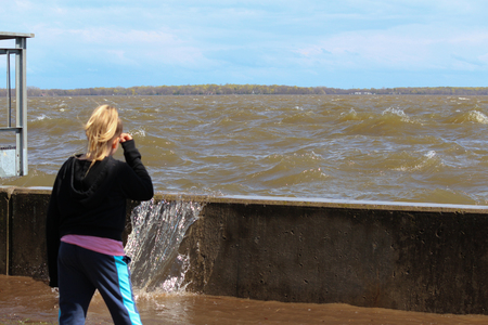 pooled: A little girl watching the waves going above the dam. Flooded area in Pointe Calumet, May 6, 2017. This is the Marina of Pointe Calumet. Editorial