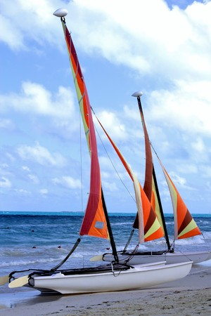 Three (3) catamarans on the beach, ready for tourists