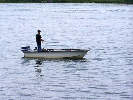 Man fishing in a boat on a lake Stock Photo