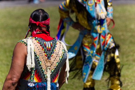 Kahnawake, Quebec, Canada - July 9, 2017: Pow Wow in Kahnawake Reserve for their 27th Annual Echoes of Proud Nation Pow Wow. Adult man dancer judges.