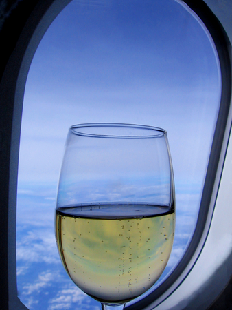 Glass of champagne in front of aircraft window-stock photos