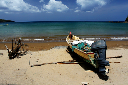 Small fishing boat on the shore in front of the beautiful sea in the Caribbeans.