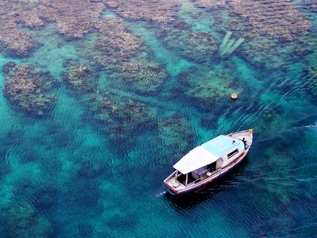 View from above of a fishing boat in the Caribbeans with clear and transparent turquoise ocean Stock Photo