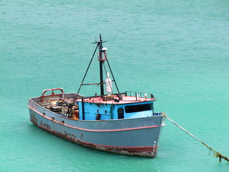 Old and rusty fishing boat anchored in the Caribbeans