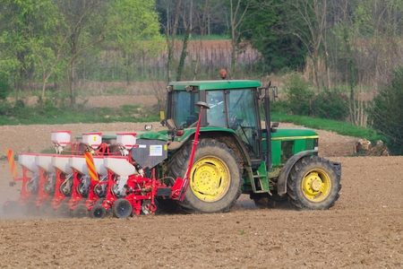 Farm tractor with seeder working in a field