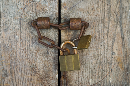 back gate: Old rusty padlock and iron chain on the wooden gate of a medieval house