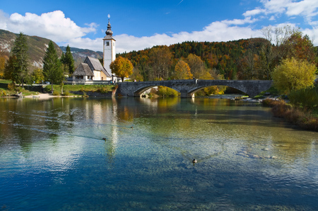 Autumn view of the stone bridge and the Church of St. John the Baptist at Lake Bohinj (Bohinjsko Jezero), Slovenia Stock Photo