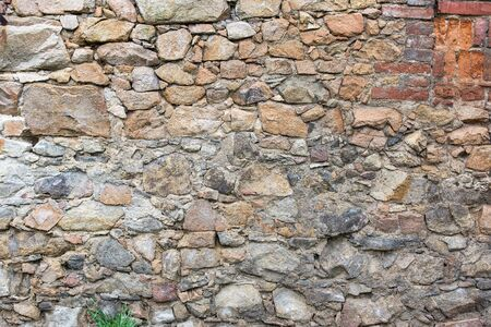 colorful old plaster wall of stones and bricks