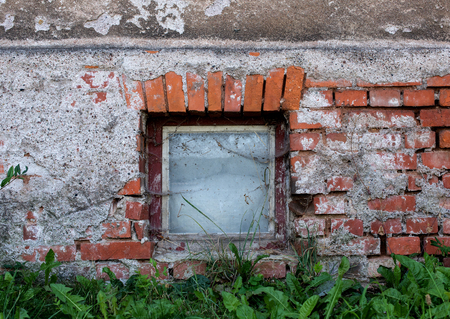 old damaged wall with a window into the cellar Stock Photo