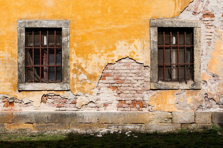 barred: old damaged yellow plastered brick wall with barred windows and a lawn