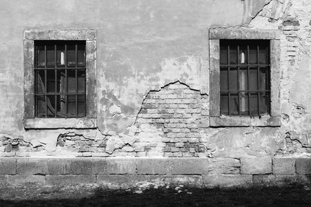 barred: old damaged plastered brick wall with barred windows and a lawn Stock Photo