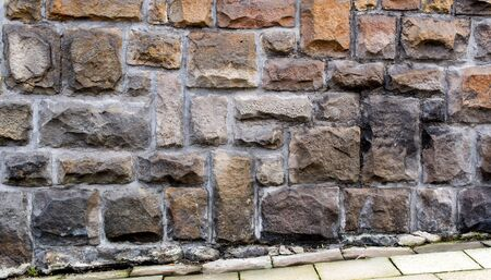 pavement: weathered stone cladded wall with pavement for background or texture Stock Photo